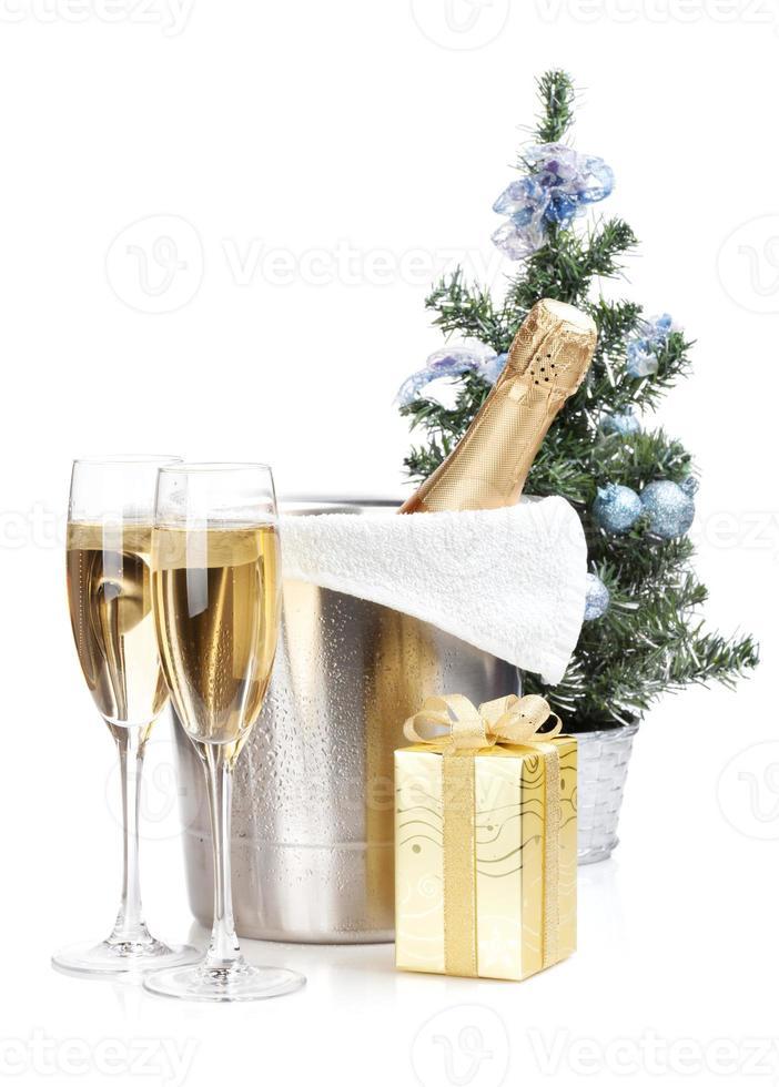 bottiglia di champagne nel secchiello del ghiaccio, due bicchieri e regalo di Natale foto