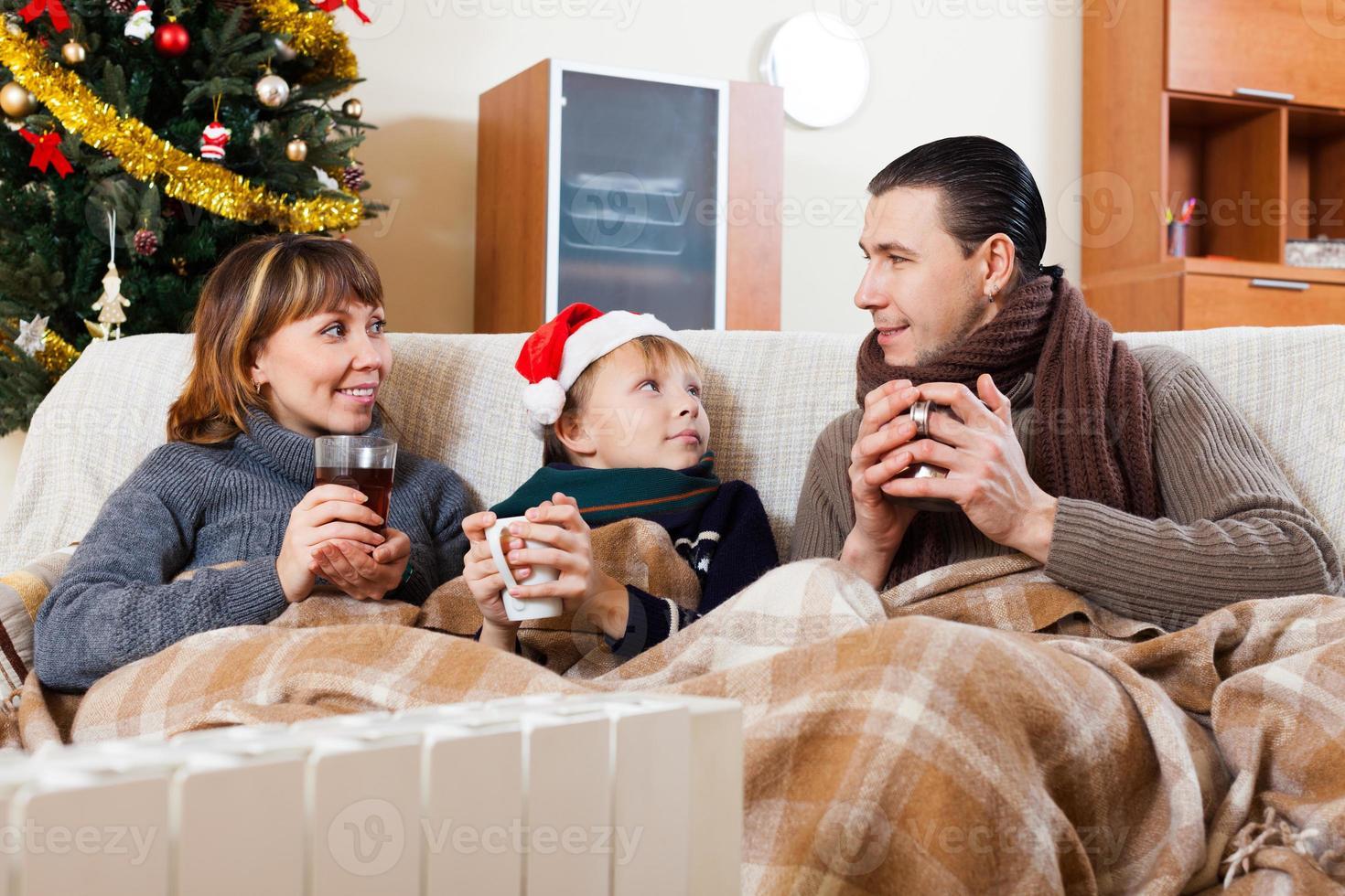 genitori e figlio che si riscaldano vicino a un riscaldatore caldo foto