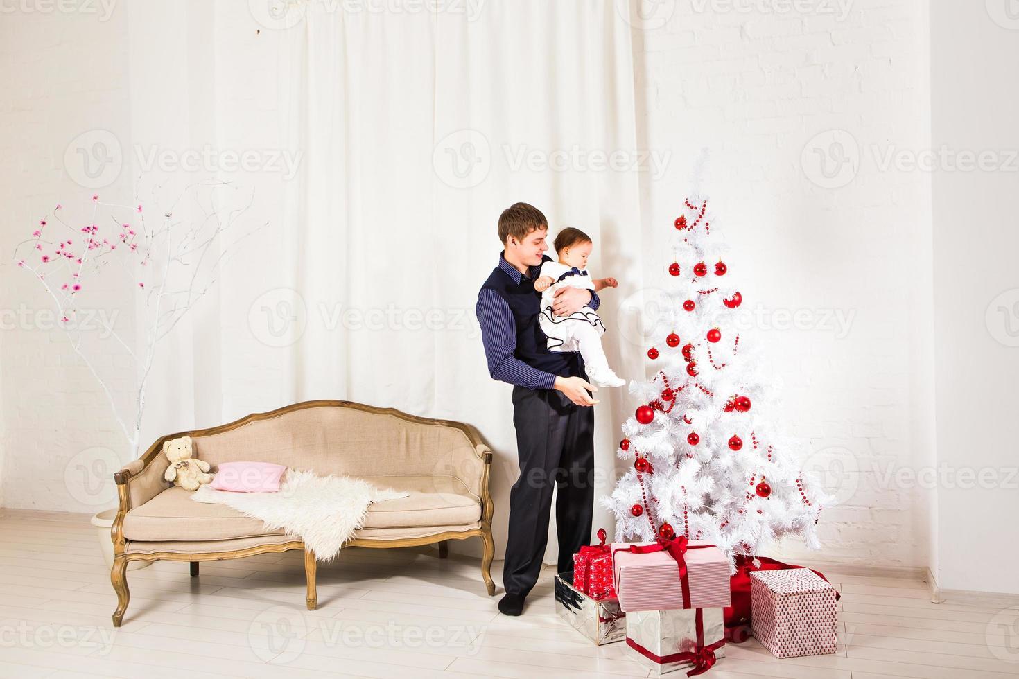 bambina gioca con suo padre vicino all'albero di Natale foto
