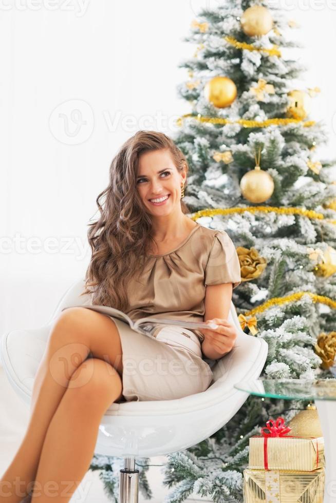 sorridente giovane donna leggendo la rivista vicino all'albero di Natale foto