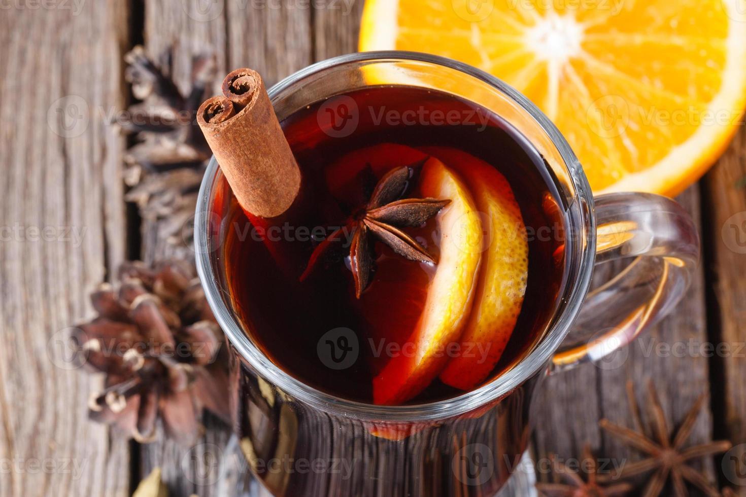 vin brulè e spezie sul tavolo in legno stagionato foto