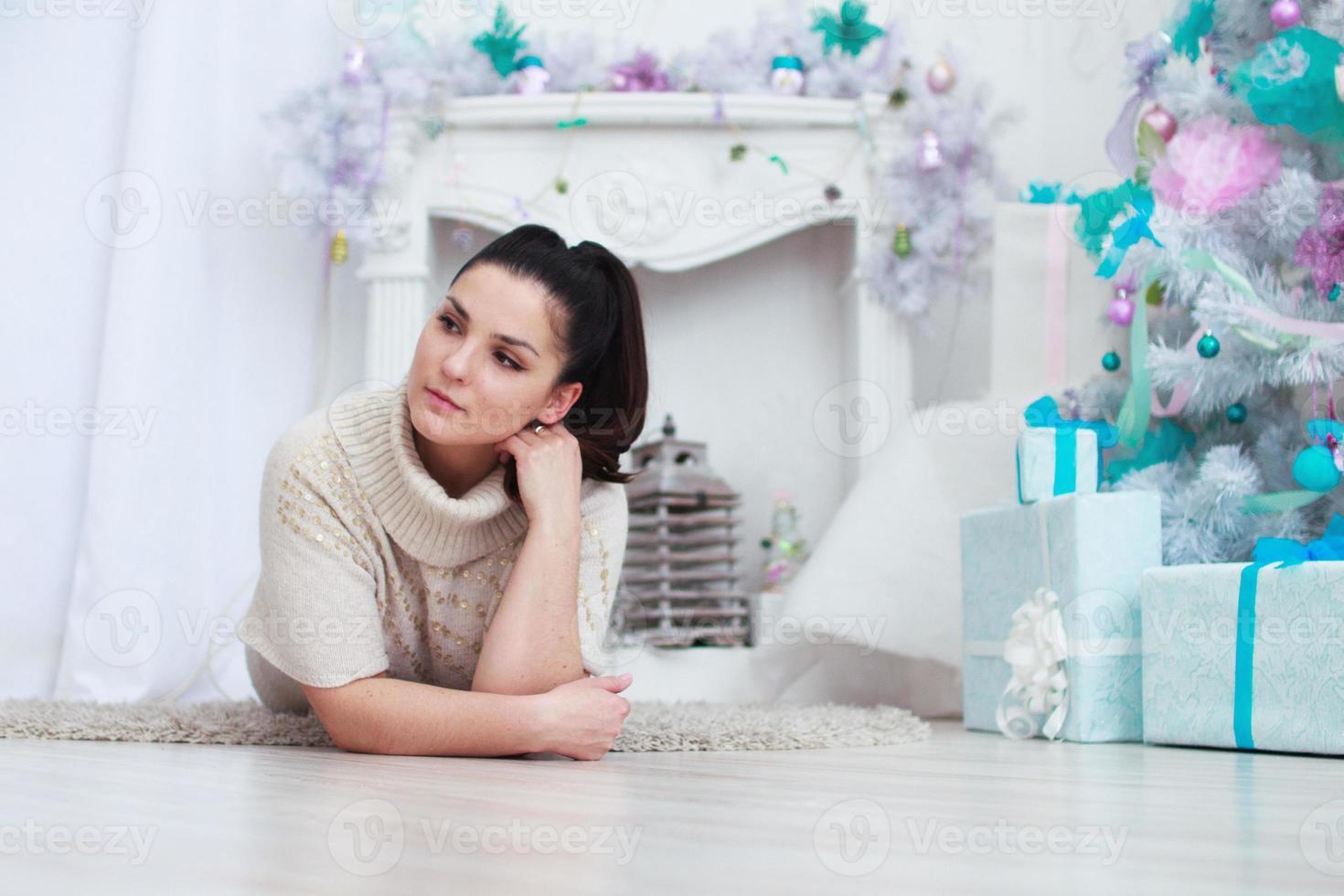 ragazza sdraiata vicino a un albero di natale bianco con doni foto