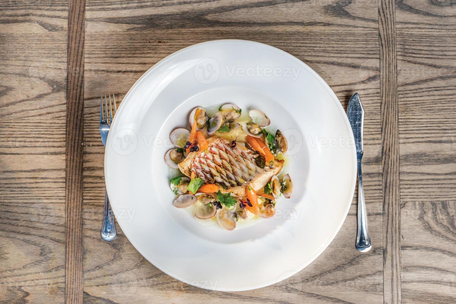 piatto di mare di pesce pappagallo al forno con carote e ostriche. foto