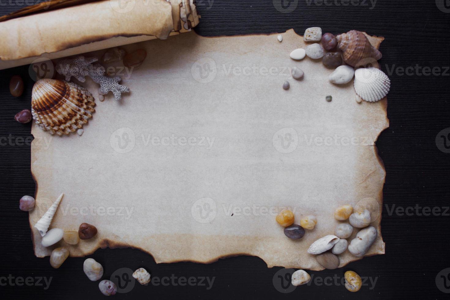 vecchio rotolo di pergamena con ciottoli di mare e conchiglie, nautico foto