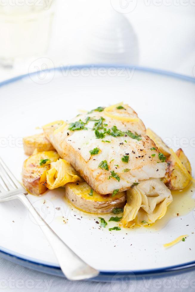 baccalà arrosto, baccalà con patate al forno e carciofi foto