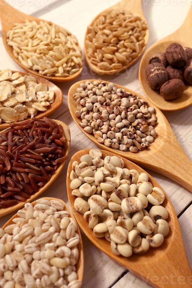 cereali nei cucchiai sul tavolo di legno bianco foto