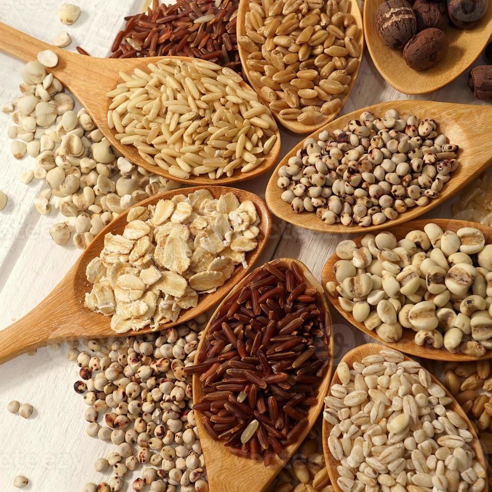 cereali, fagioli nei cucchiai sul tavolo di legno bianco foto