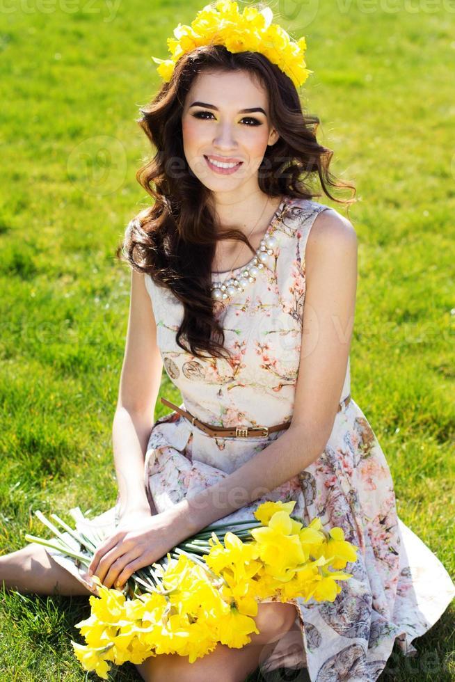 ragazza sorridente felice con fiori gialli foto
