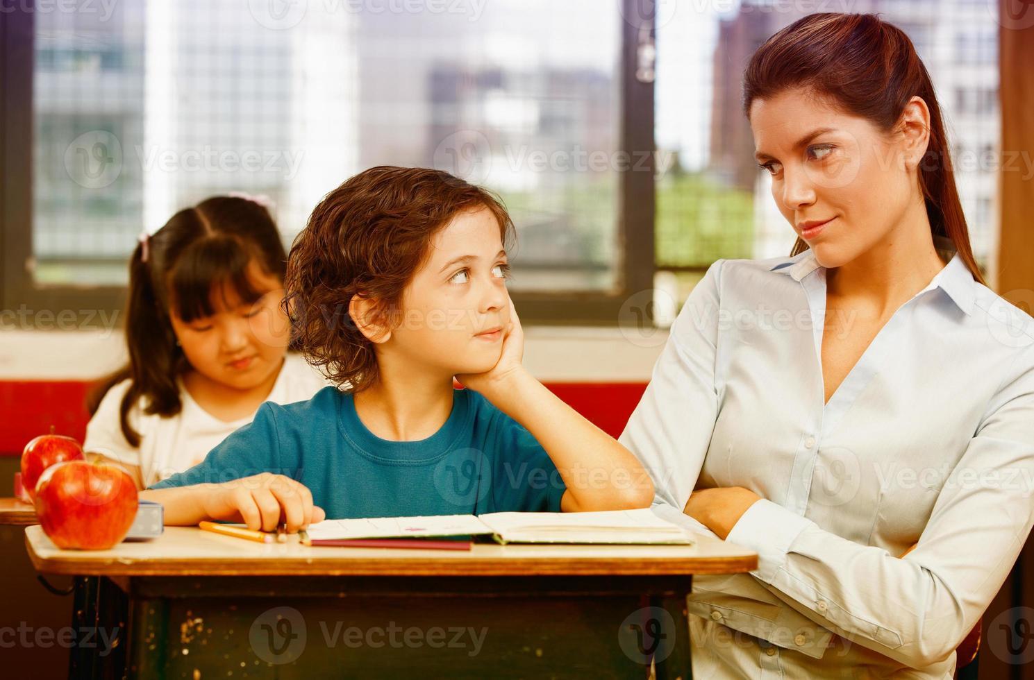 insegnante e scolaro che si guardano nell'aula primaria foto