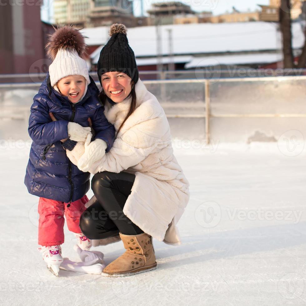 sorridente giovane madre e la sua piccola figlia pattinaggio su ghiaccio insieme foto