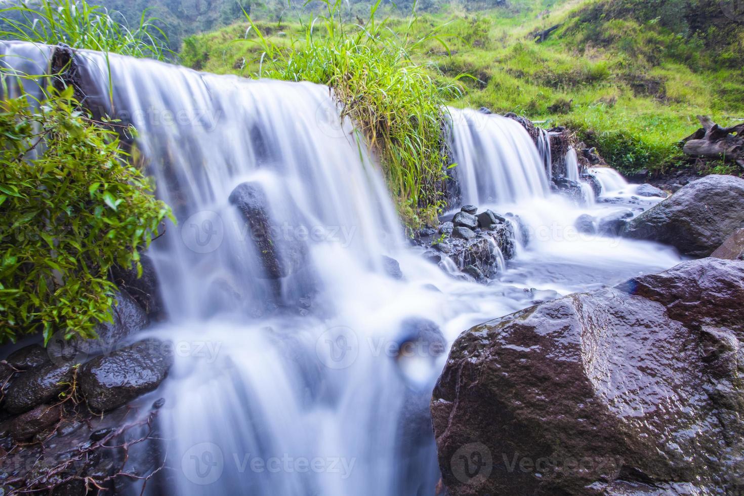 cascata a bassa velocità con collina verde e rocce foto