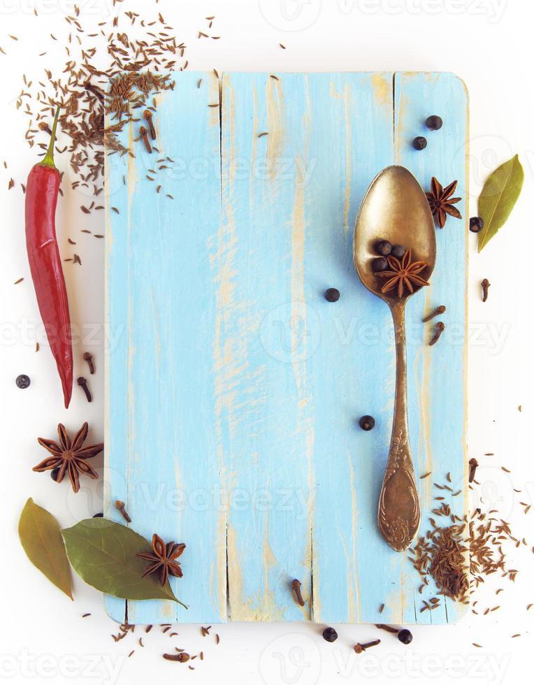 spezie diverse, anice, alloro, chiodi di garofano e altri su tavola di legno foto