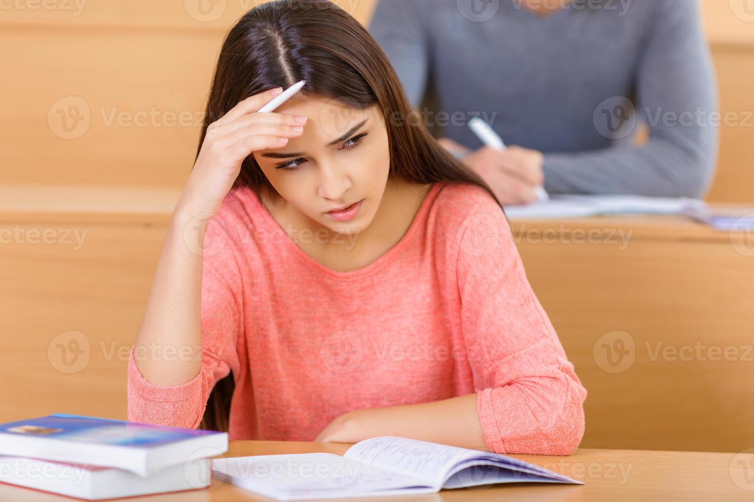 attraente ragazza studentessa sembra preoccupata foto