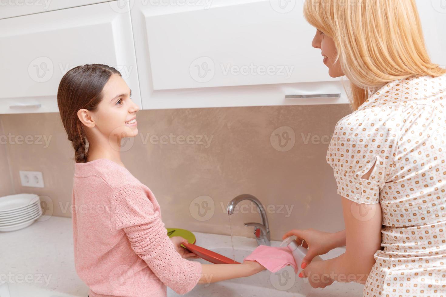 madre e figlia lavano i piatti foto