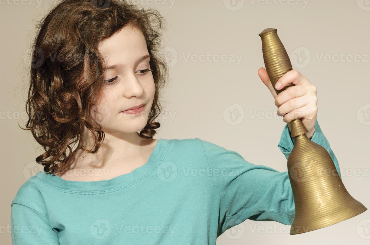 ragazza suona il campanello della scuola foto