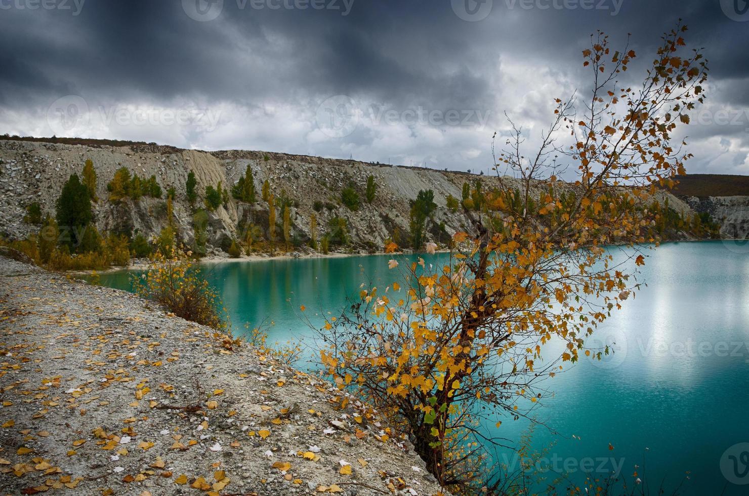 lago turchese con alberi che crescono sui pendii foto
