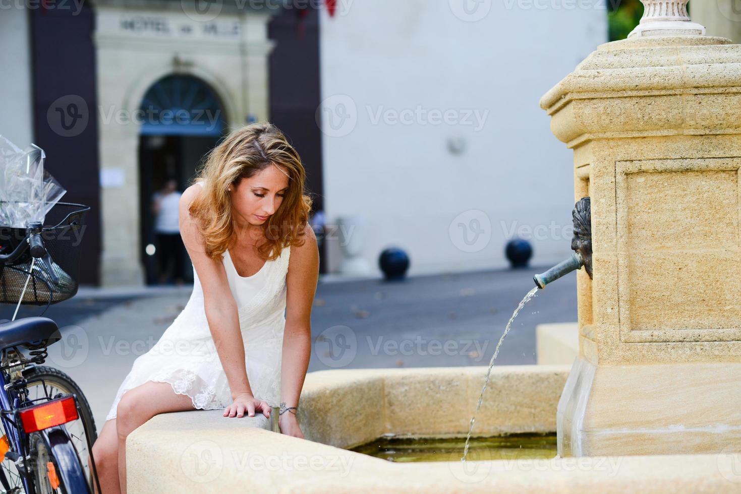attraente giovane donna romantica che gioca con l'acqua in estate lavatoio foto