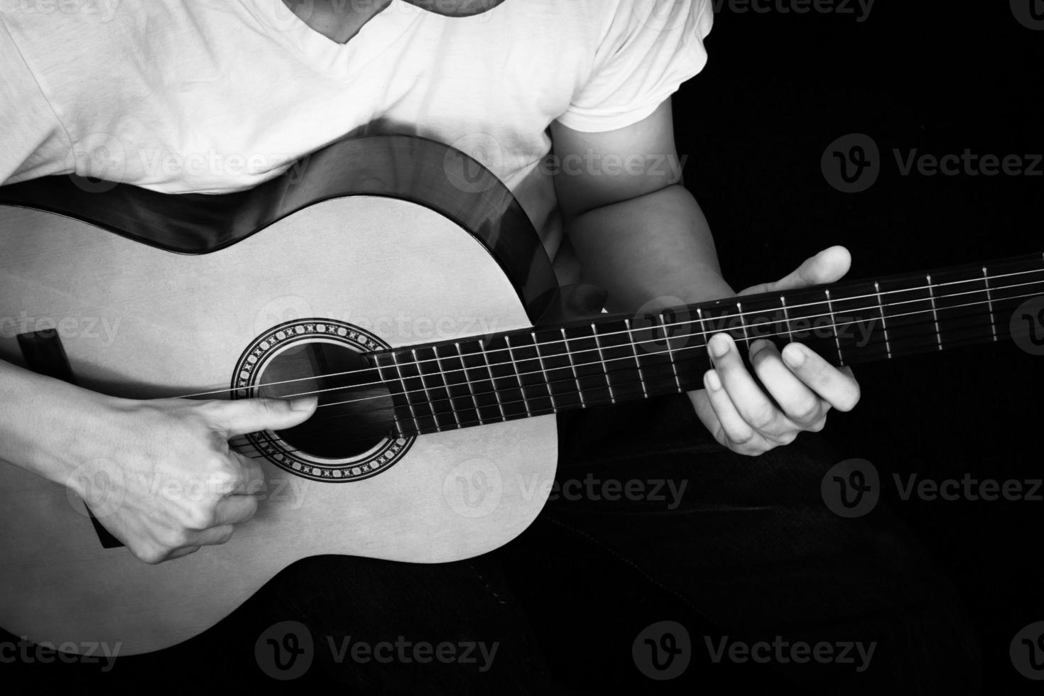 musicista asiatico suona la chitarra acustica foto