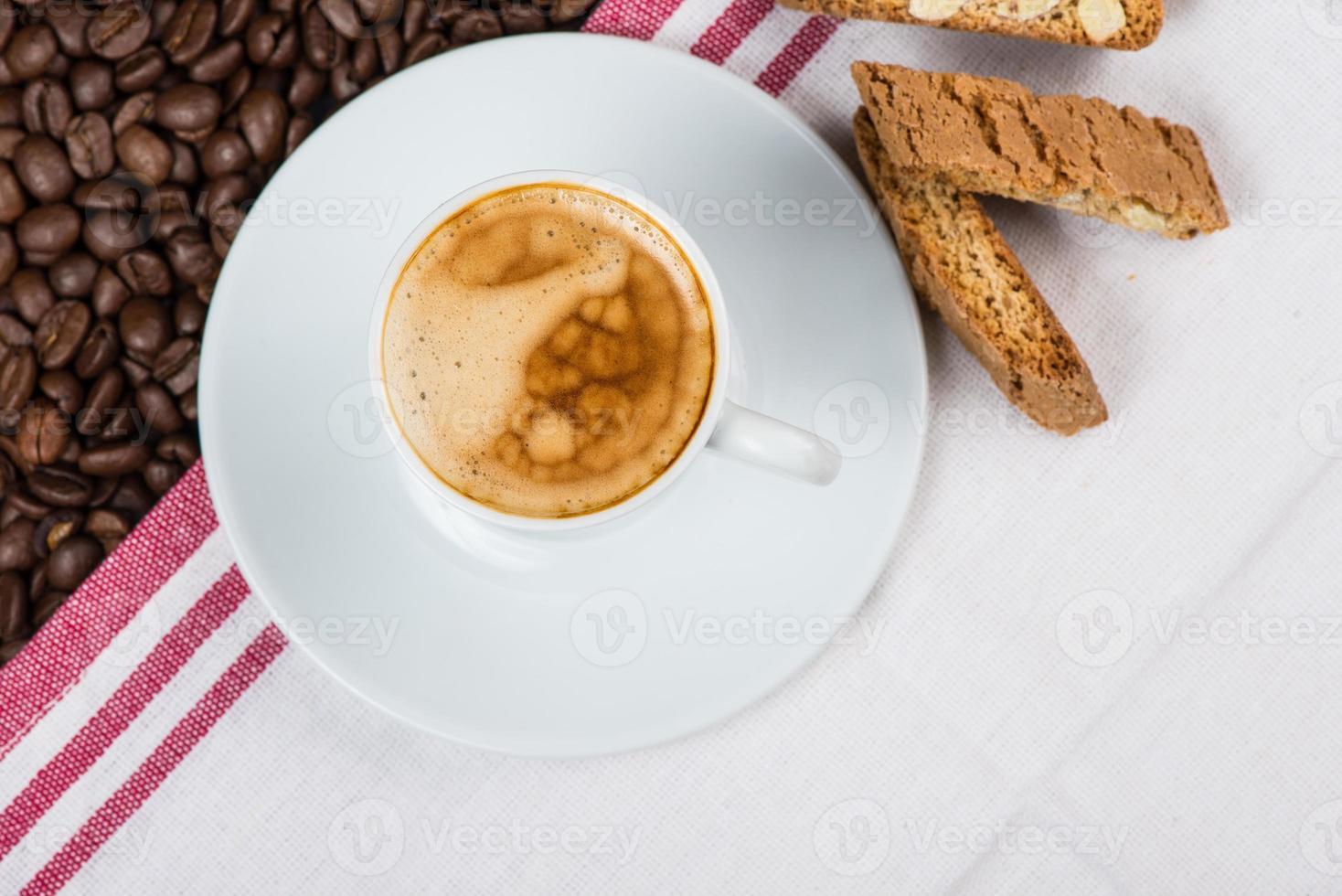 tazza di caffè espresso cremoso su chicchi di caffè tostati foto