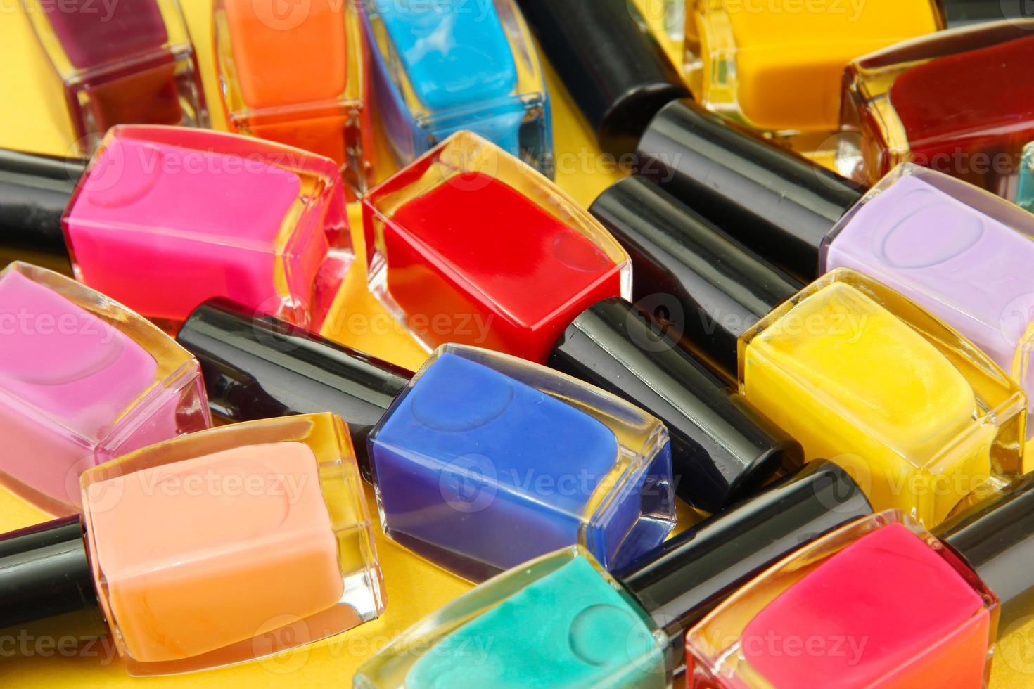 gruppo di brillanti smalti per unghie, su sfondo giallo foto