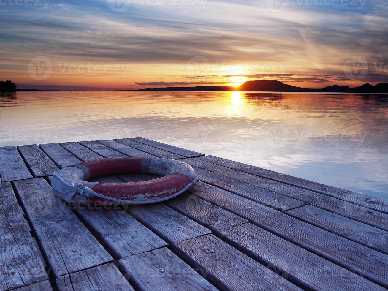 cintura di salvataggio sul molo al tramonto foto