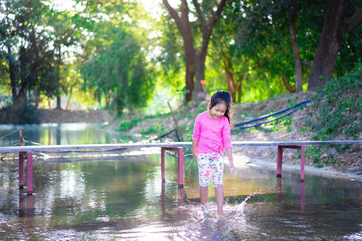 piccola ragazza asiatica che gioca in acqua foto