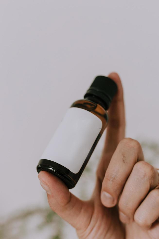 mano che tiene una bottiglia di vetro vuota foto