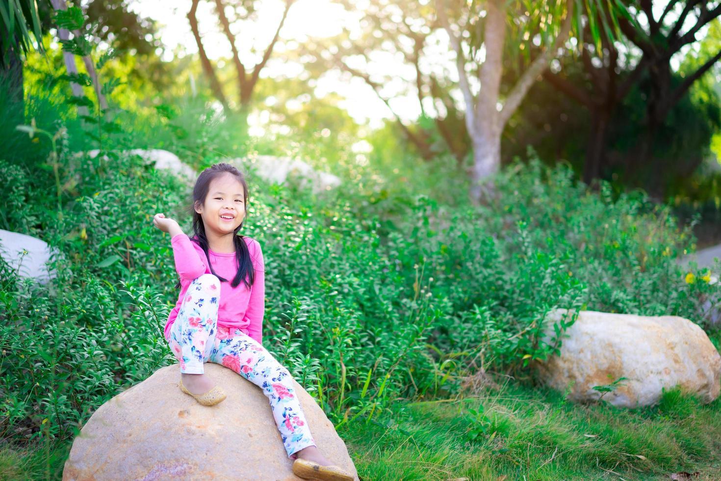 ragazza asiatica felice che si siede sulla roccia con la luce solare foto