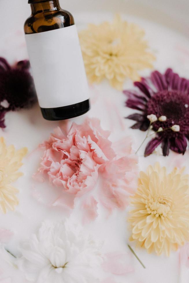 bottiglia vuota del prodotto sopra latte e fiori foto