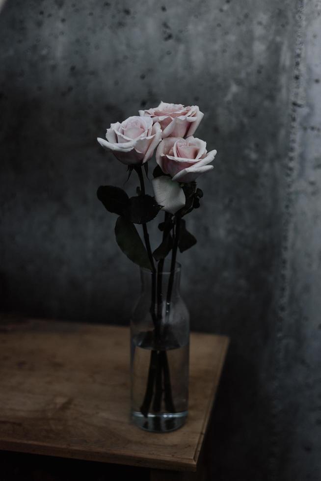 tre rose rosa in vaso di vetro sul tavolo foto