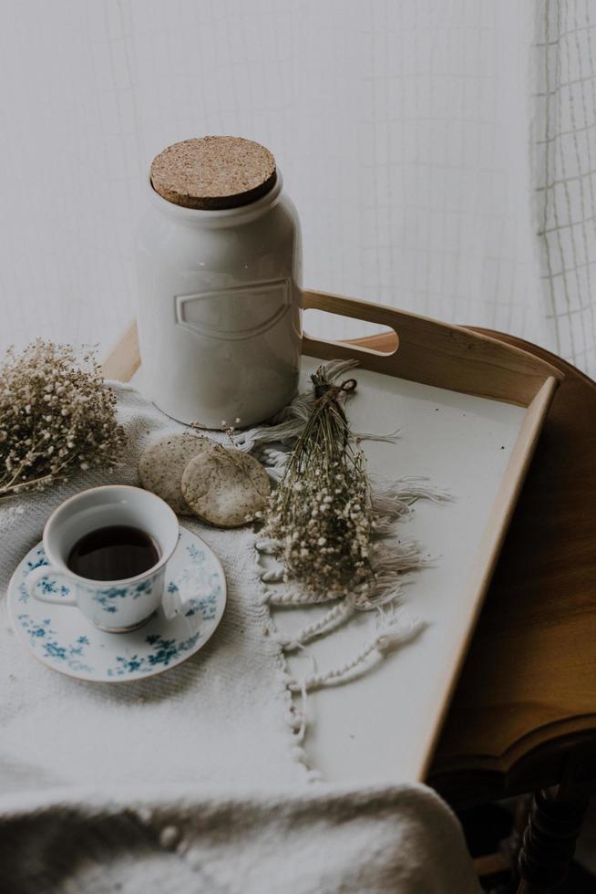 piattino, tazza e contenitore sul vassoio vicino alla finestra foto