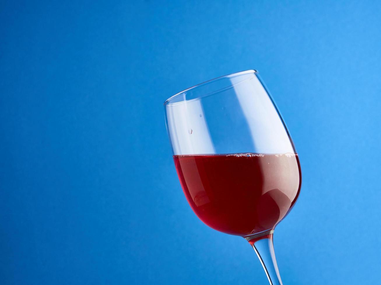 bicchiere di vino rosso su sfondo blu foto