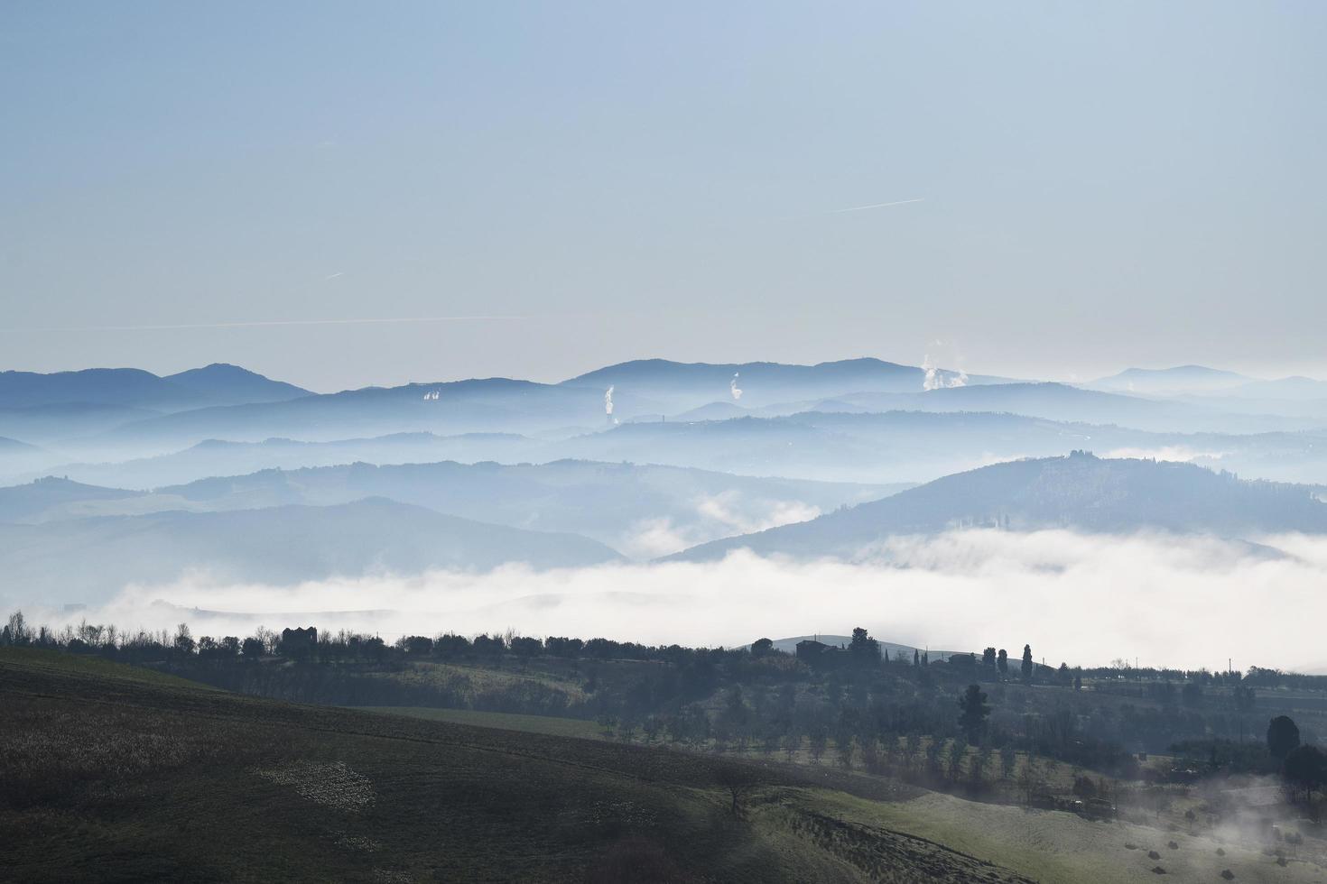 campo di erba nebbiosa sotto il cielo blu durante il giorno foto