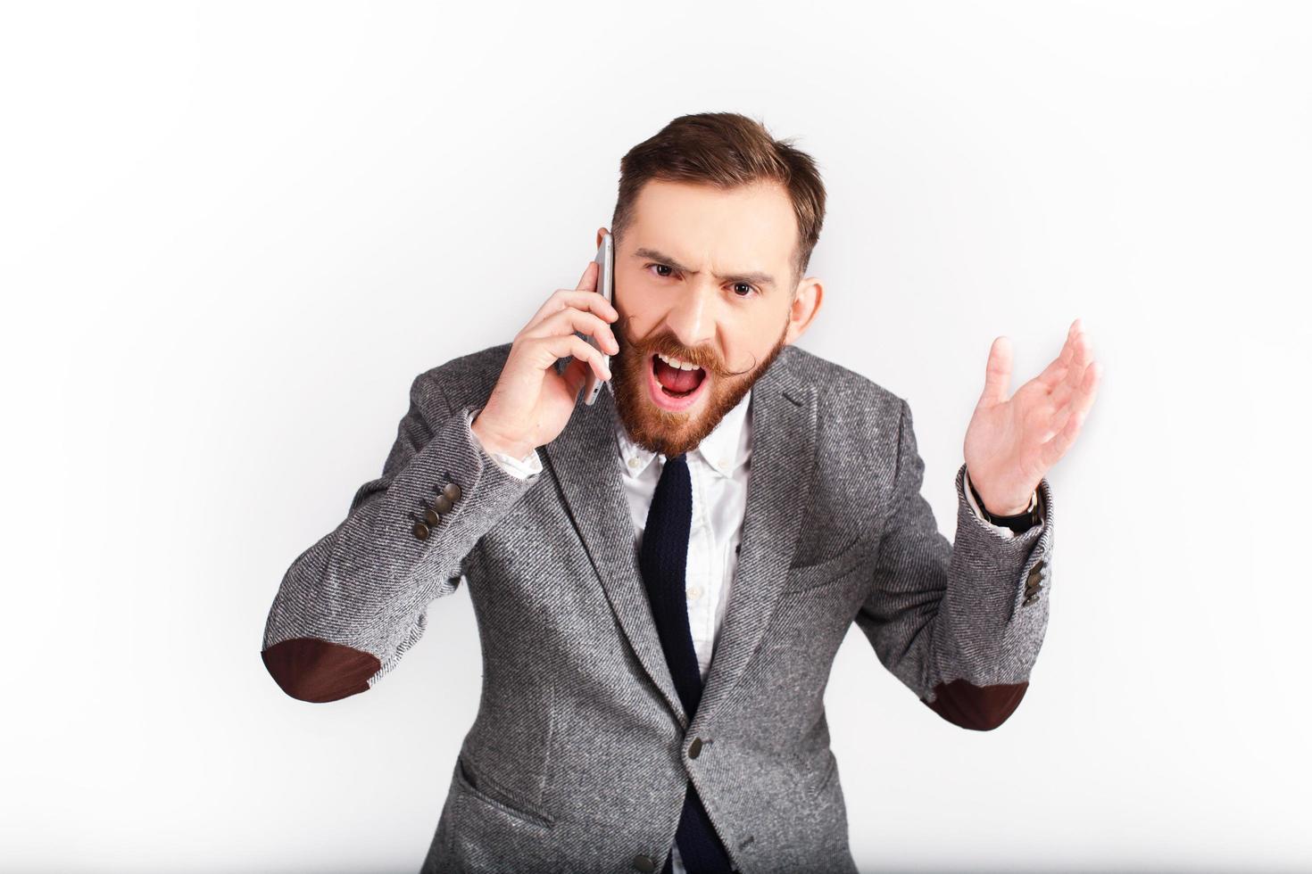 uomo arrabbiato in abito grigio parla al telefono foto