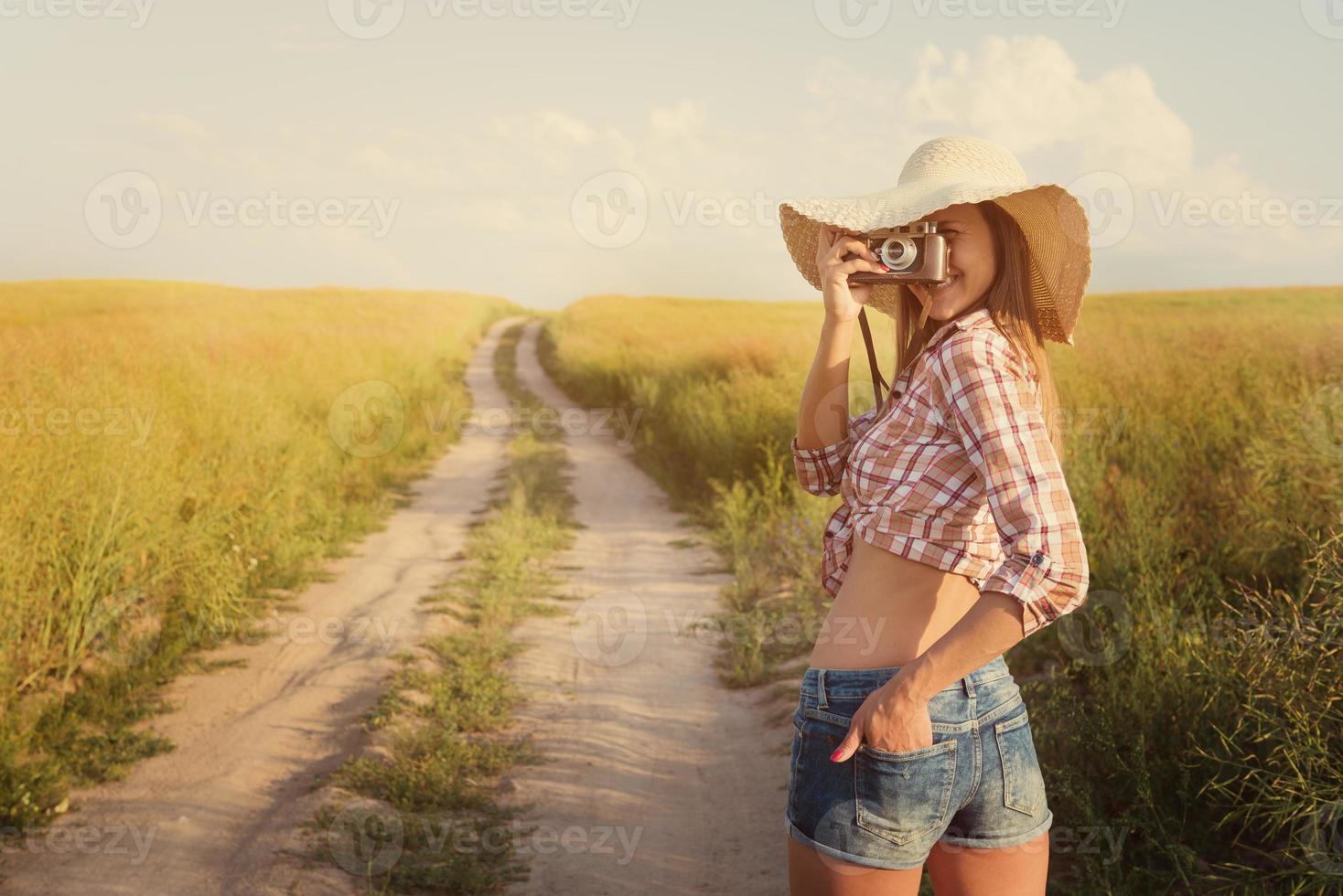 bella ragazza con fotocamera retrò su strada di campagna, instagra foto