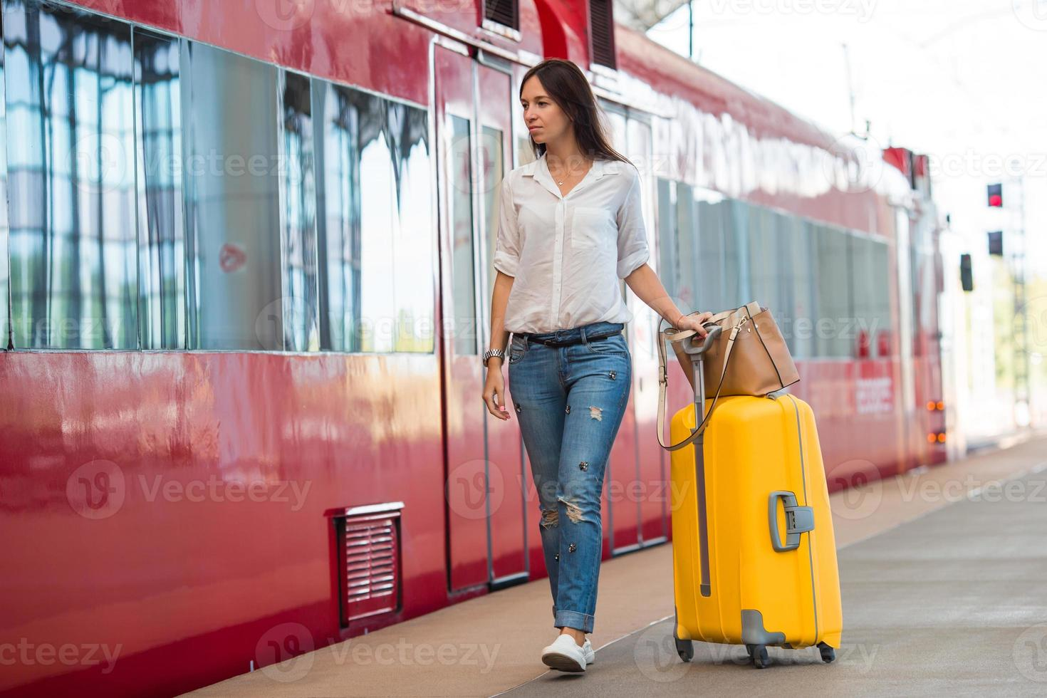 giovane donna felice con i bagagli in una stazione ferroviaria foto