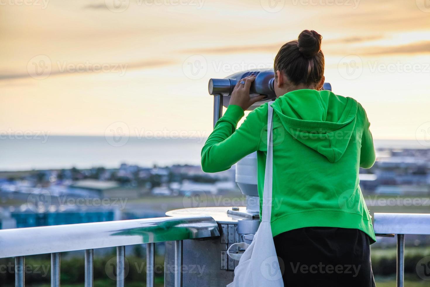 giovane ragazza guardando attraverso un binocolo pubblico a gettoni foto