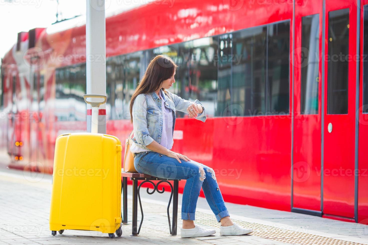 giovane bella ragazza con bagagli in una stazione ferroviaria foto