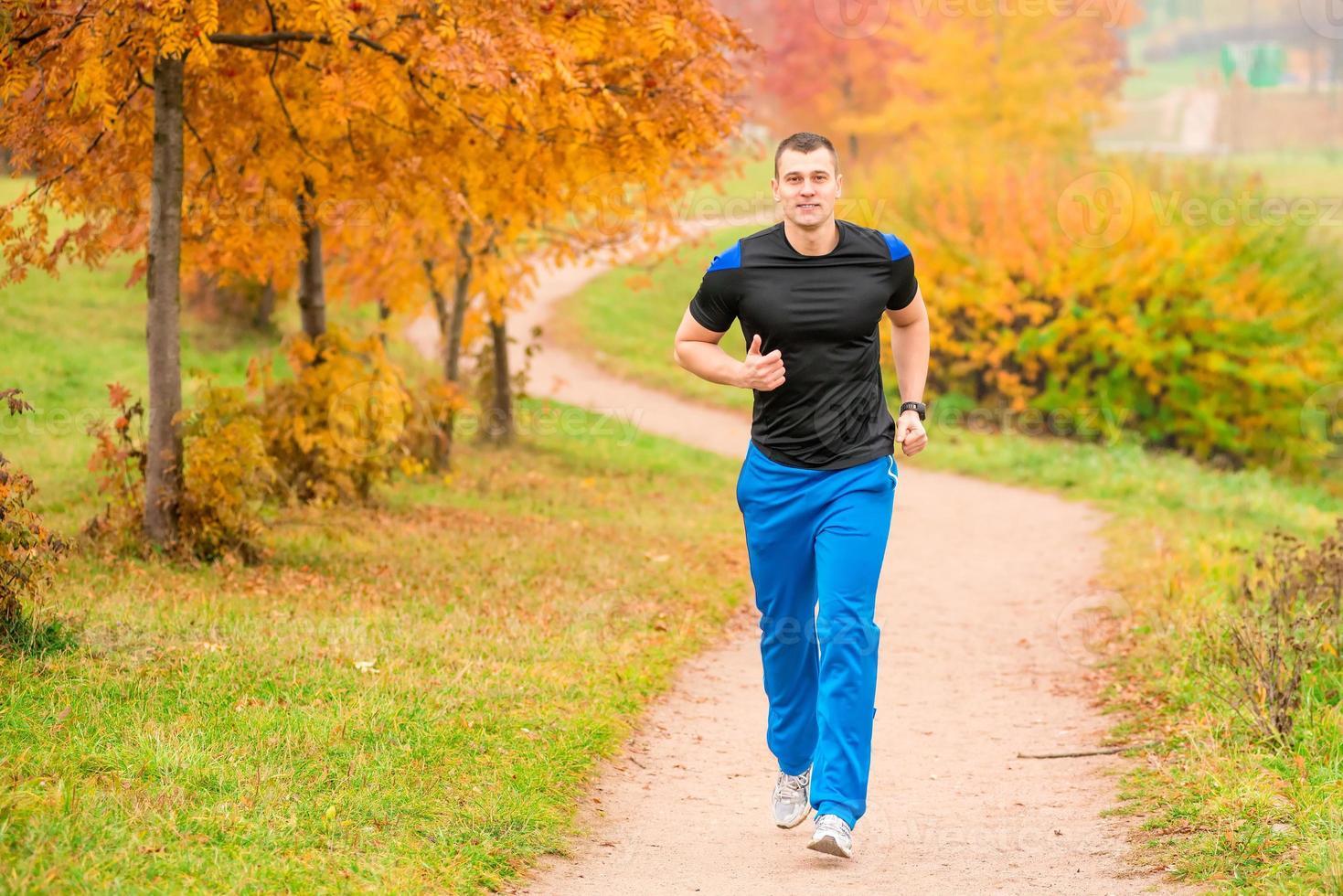 uomo atletico che corre nel parco su un sentiero foto