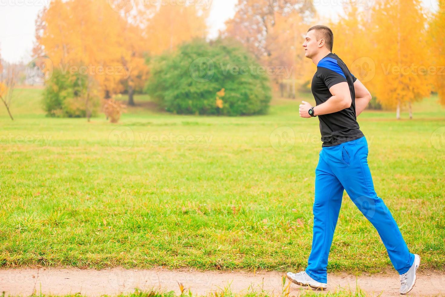 atleta maschio fare jogging al mattino nel parco foto