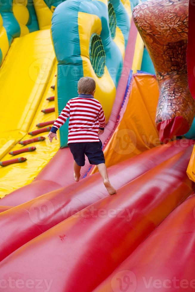 bambino di quattro anni che gioca su un trampolino foto