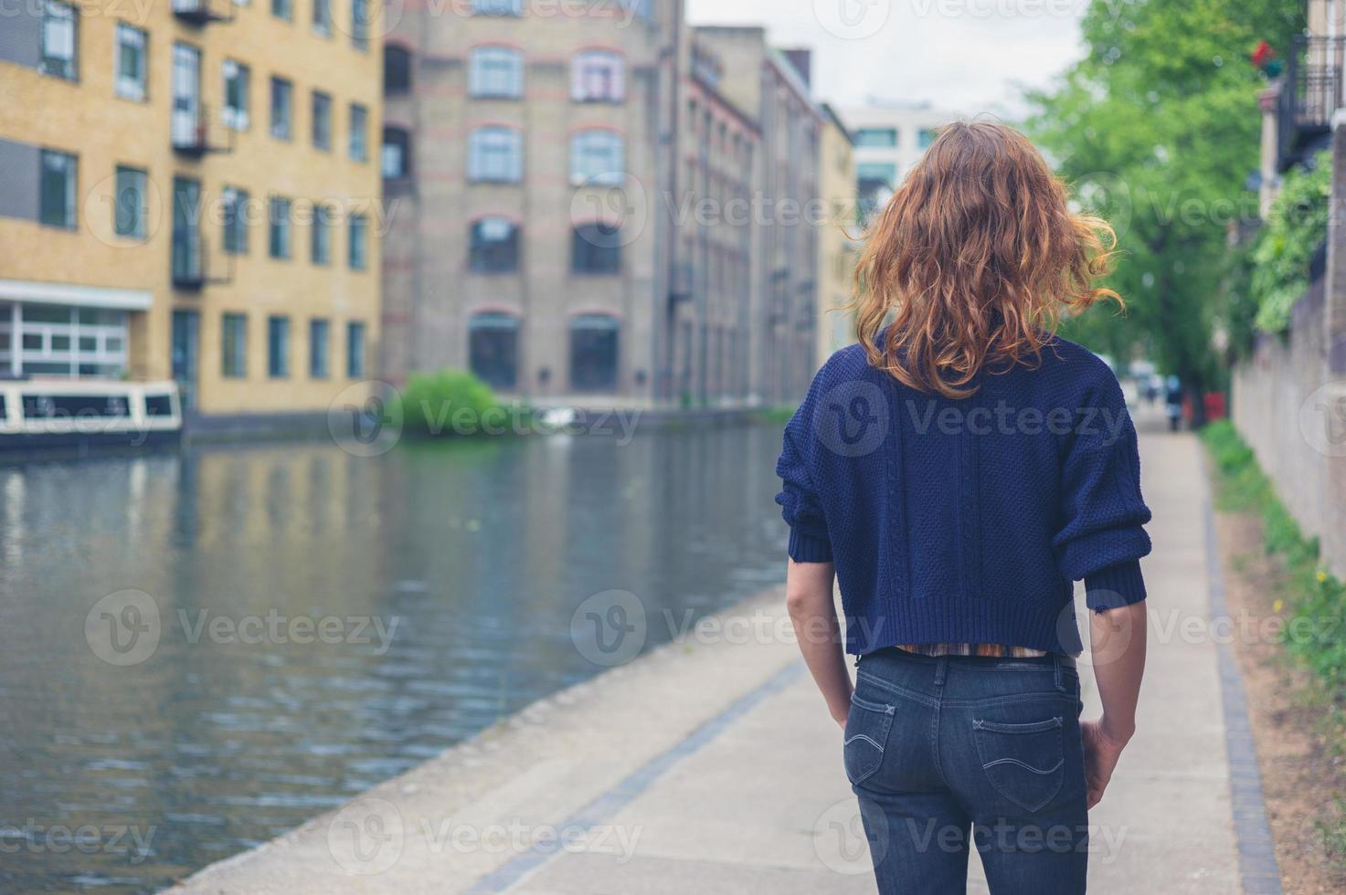 giovane donna che cammina dal canale in città foto