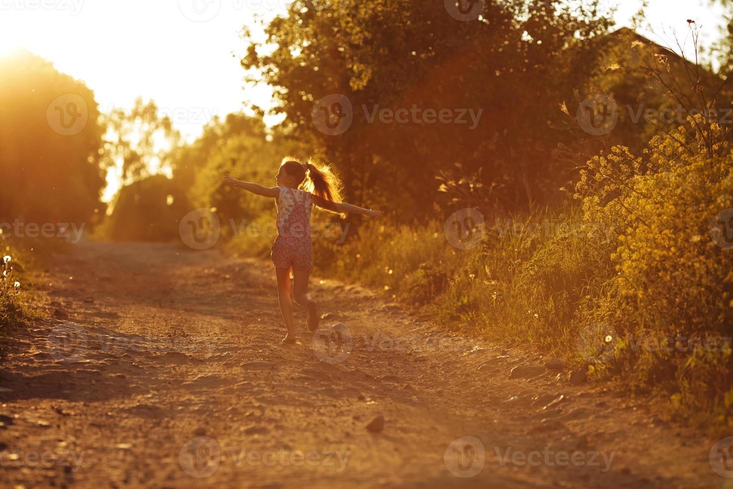 bambina felice che corre lungo una strada di campagna foto
