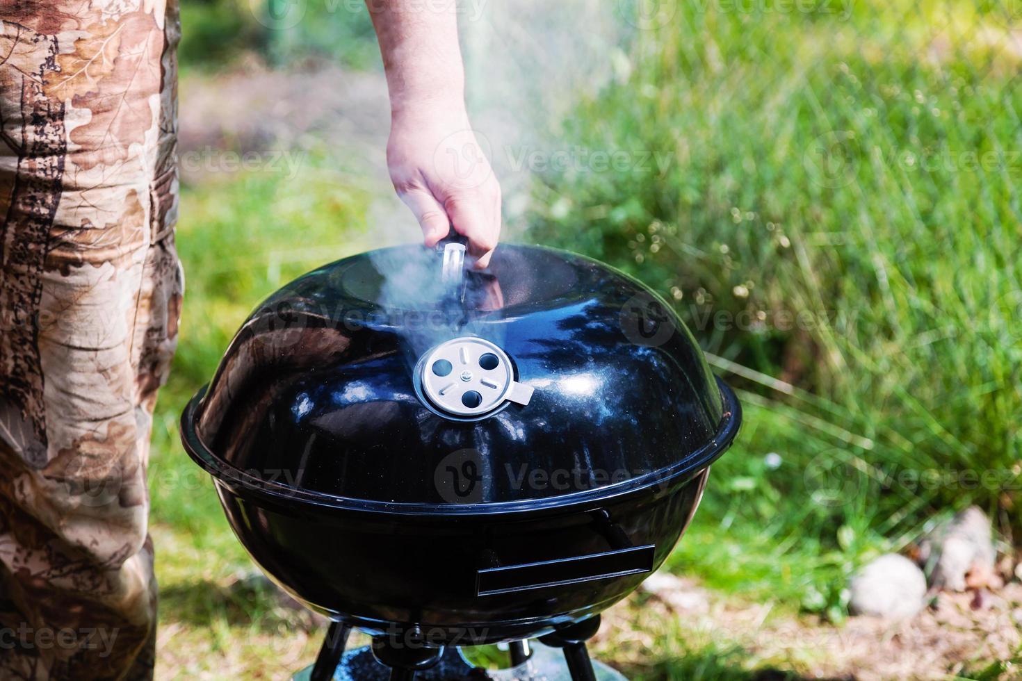 chef mano che tiene il coperchio chiuso grill foto