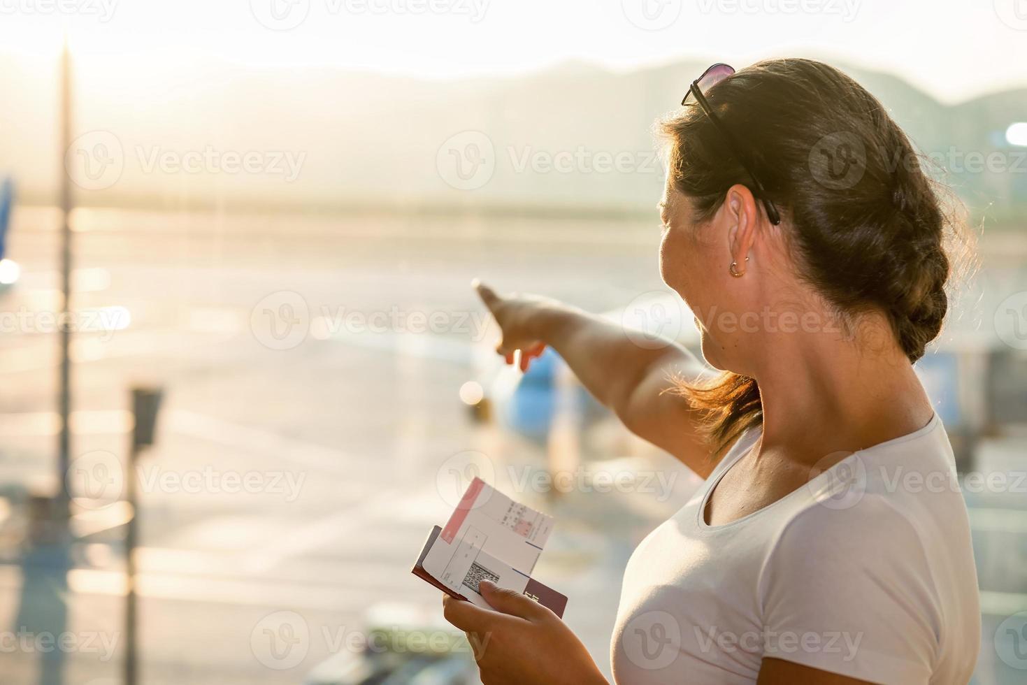 bella bruna che mostra un aereo in aeroporto foto