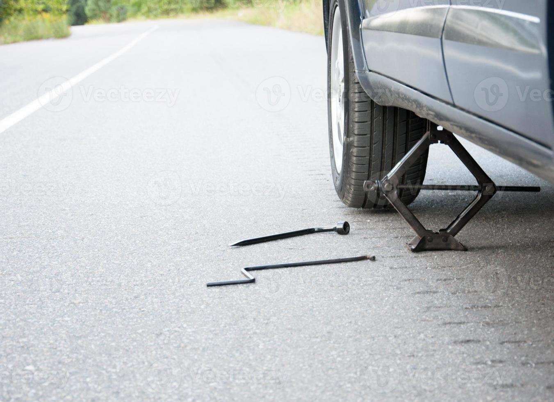 cambiando la ruota dell'auto sulla strada foto