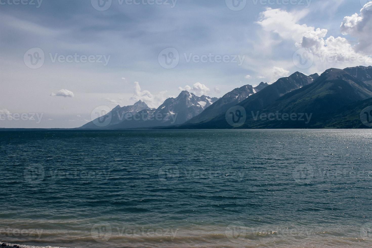 montagne glaciali in lontananza grande base blu cristallina del lago nuvoloso foto