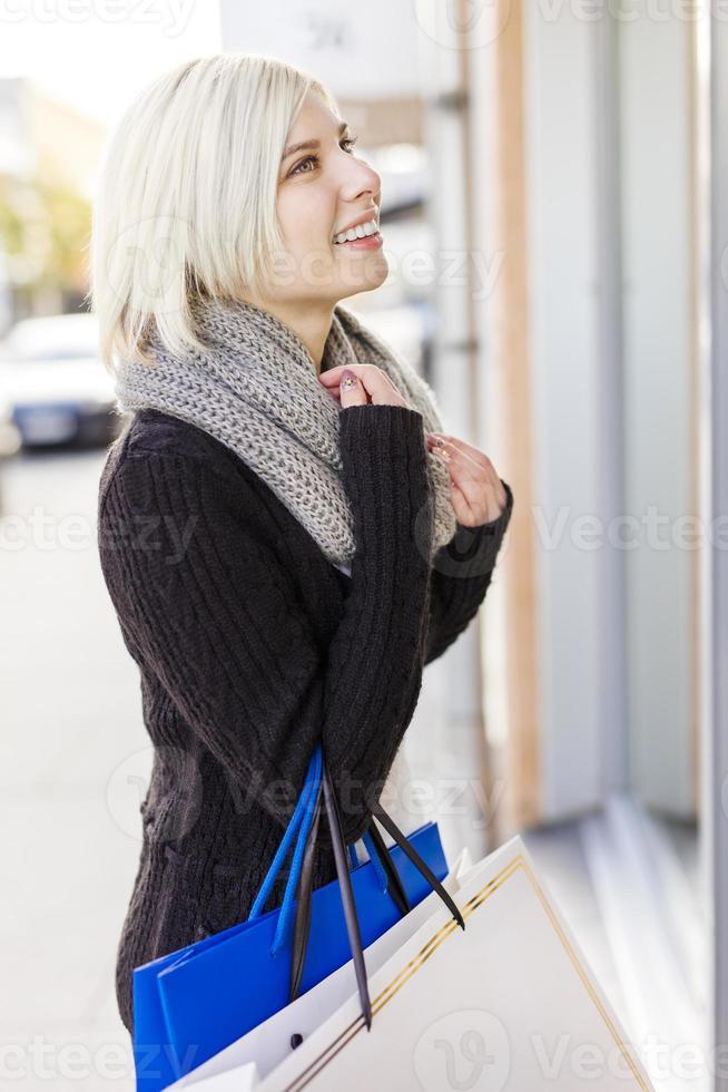 donna sorridente fuori a fare shopping in città foto