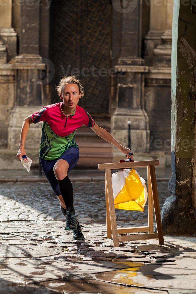 donna punzonatura al punto di controllo che partecipa a gare di orienteering foto