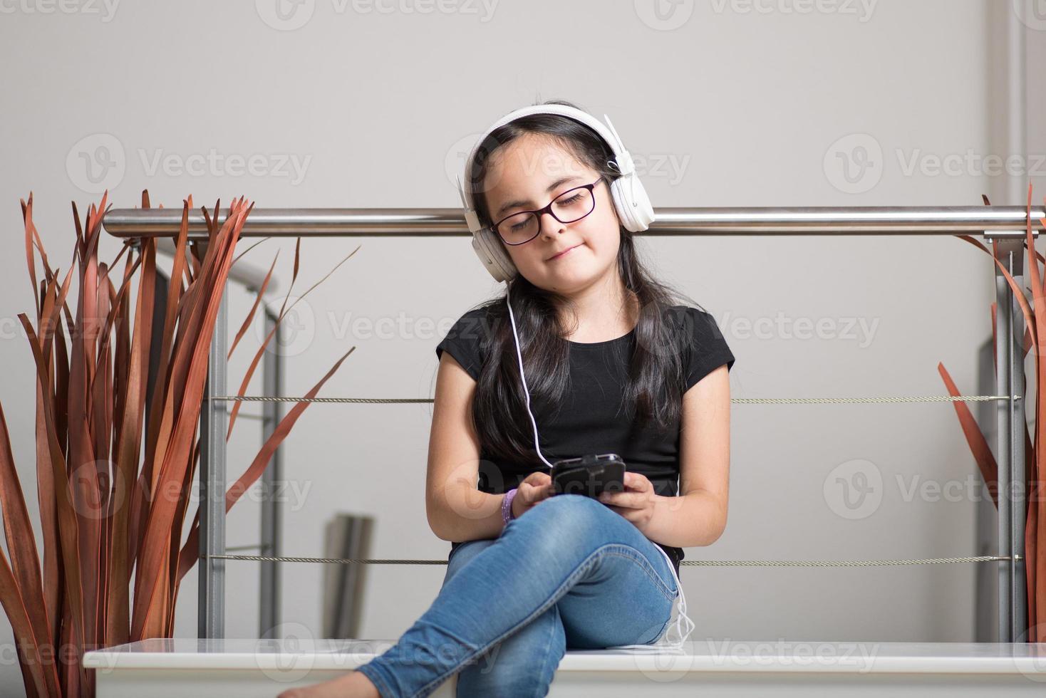 ragazza carina con gli occhiali che ascolta la musica foto